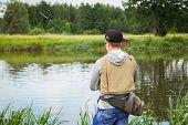 pic of fishermen  - Fisherman on the river bank in sunglasses - JPG