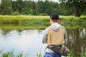 image of fisherman  - Fisherman on the river bank in sunglasses - JPG