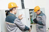 pic of electrical engineering  - electrician builder engineer workers with electric cable wiring of fuse switch box - JPG