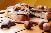image of hazelnut  - Two slices of bread with chocolate cream and hazelnuts on a wooden table - JPG