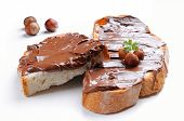 stock photo of hazelnut  - Two slices of bread with white chocolate cream and hazelnuts isolated front view - JPG