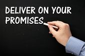 stock photo of promises  - Male hand wearing a business shirt writing the phrase Deliver On Your Promises in white text on a blackboard - JPG