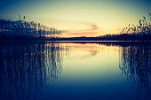 image of calming  - Vintage photo of beautiful sunset over calm lake - JPG