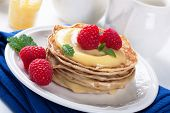 stock photo of curd  - Delicious pancakes with homemade lime curd and fresh raspberries - JPG
