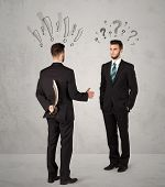 picture of backstabbers  - Ruthless businessman handshake with drawn exclamation and question marks around them head - JPG