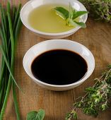 stock photo of vinegar  - Olive oil balsamic vinegar and herbs on a vintage wood background - JPG