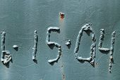 image of scrap-iron  - Iron surface painted in blue with numbers in relief and rusty spots - JPG