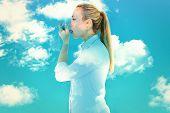 image of asthma inhaler  - Beautiful blonde using an asthma inhaler against blue sky - JPG