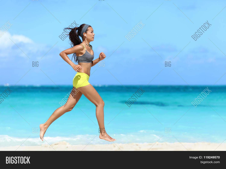 Fit Female Athlete Runner Running On Beach Full Length Body Of Woman Jogging Fast
