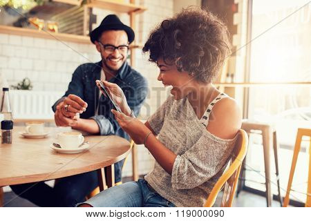 Cheerful Woman Using Digital Tablet With A Friend At Cafe
