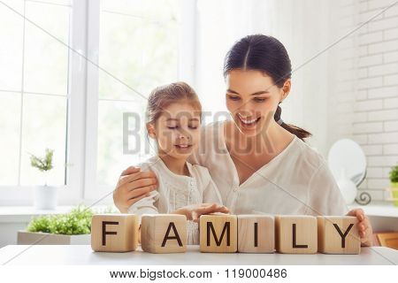 Happy loving family playing with blocks and having fun. Blocks have letters. Mother and her daughter lay out cubes and word family.