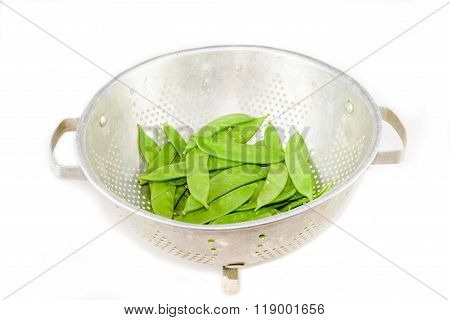 Clean Snow Peas In The Colander On The White Background