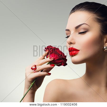 Beauty Woman with red rose. Fashion Model Girl face Portrait with Red Rose in her hand. Red Lips and Nails. Beautiful Luxury Makeup and Manicure. Vogue Style