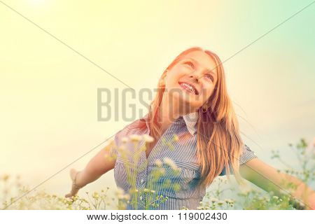 Beauty Girl Outdoors enjoying nature. Beautiful Teenage Model girl having fun on spring Field with blooming flowers, raising hands in Sun Light. Sunrise. Glow Sun. Free Happy Woman, allergy free
