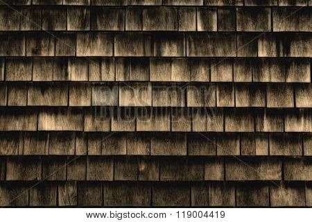 A background of ancient wood shingles in warm wood tones.