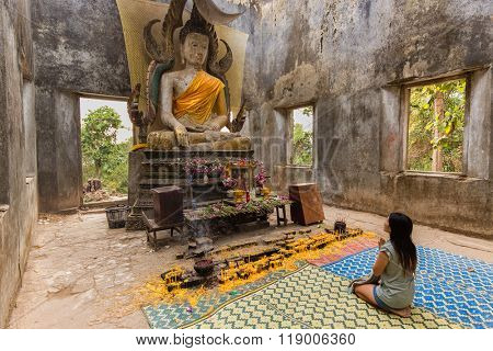Thai woman praying in the ancient hidden temple of Wat Som Ded in Sangkhlaburi, Thailand