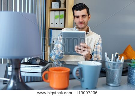 Young businessman using tablet pc, sitting at desk, smiling.