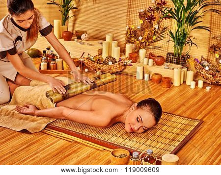 Woman getting bamboo luxury massage on wooden floor.
