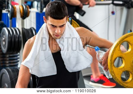 Strong man looking down and  work with  dumbbells his body at gym. Portrait of handsome man.