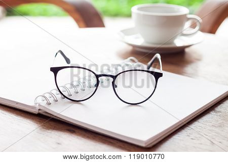 Open Blank White Notebook And Eyeglasses With Cup Of Coffee