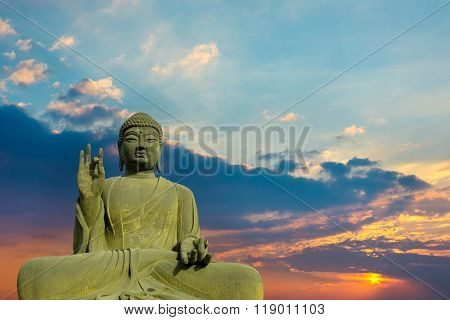 Statue Of Buddha At Peace With Sunset Background.