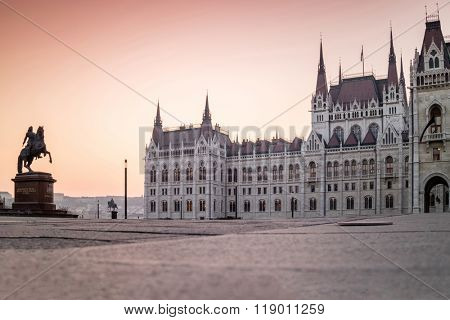 The Hungarian Parliament Building in Budapest and the view at an empty square and the statue of Francis II Rakoczi at dawn