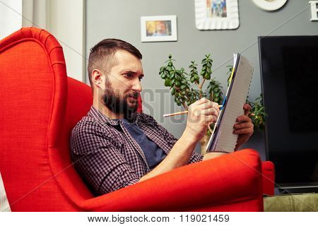 pensive young man with notepad at home