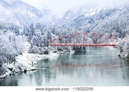 Red Bridge with winter landscape along Tadami River in Fukushima Japan