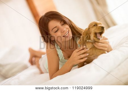 Pretty young female owner of the puppy gently caressing him in bed