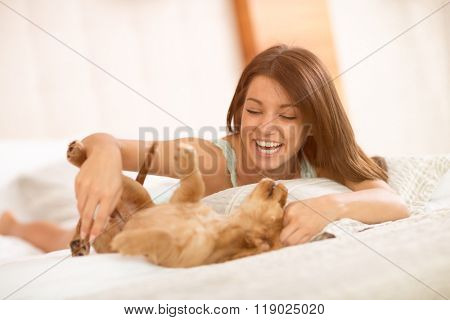 Very happy brunette play with her adorable puppy pet in bedroom