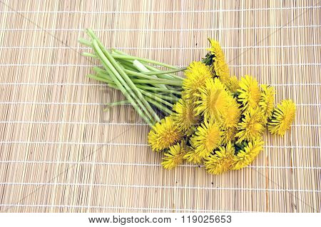 Bouquet Of Fresh Dandelions On Bamboo Mat
