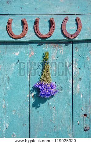 Three Horseshoes And Bunch Of Cornflowers Hanging On Oldwooden Door