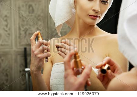 Attractive woman applying parfume.
