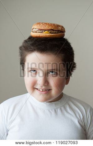 boy smiling and want to eat a burger that is on his head