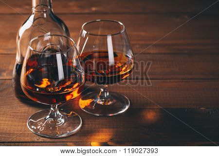 Two Glasses Of Cognac And Bottle On The Wooden Table.