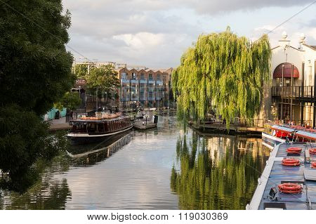 LONDON UK - 17TH JULY 2015: A view along Regents Canal in central London during the day in the Summer. People boats locks and Barge can be seen.