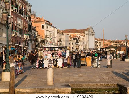 VENICE ITALY - 13TH MARCH 2015: Part of Riva degli Schiavoni in Venice during the day showing large amounts of people building exteriors and market stalls
