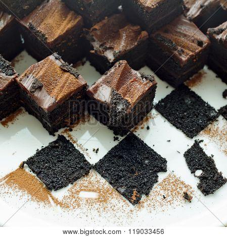 Cake chocolate brownies on white plate with leavings of brownies
