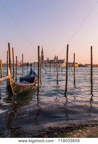 The Church of San Giorgio Maggiore from the main Venice waterfront showing wooden posts and a Gondola in the foreground