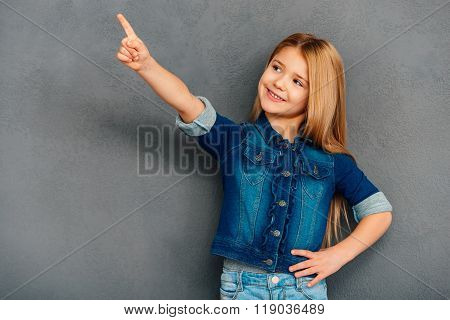 Take a look here! Cheerful littlegirl pointing away and smiling while standing against grey background