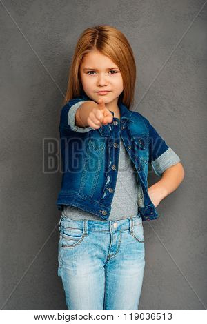 You did it! Beautiful littlegirl pointing you and looking at camera while standing against grey background