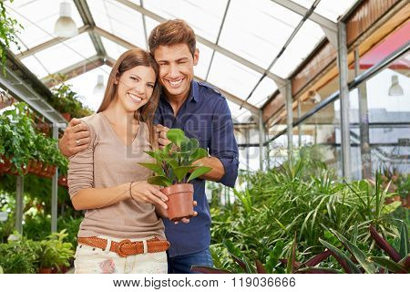 Happy couple buying a green plant in garden center