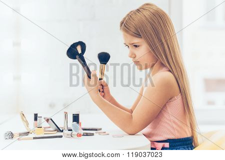 Side view of pensive little girl choosing one of two make-up brushes while sitting at the dressing table.