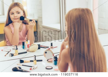 Cheerful little girl applying make-up and looking at her reflection in mirror while sitting at the dressing table ** Note: Soft Focus at 100%, best at smaller sizes