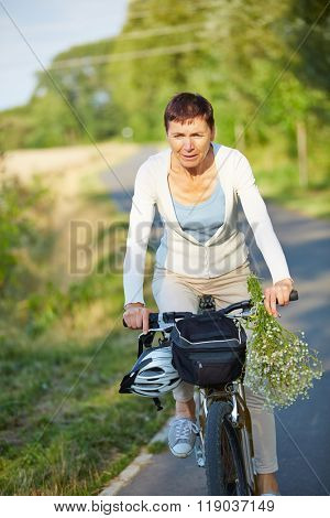 Senior woman on a bike trip with her bicycle in summer