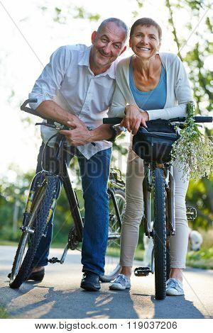 Two smiling senior people taking a bike tour together in summer