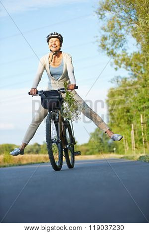 Smiling old woman stretching her legs while cycling in summer