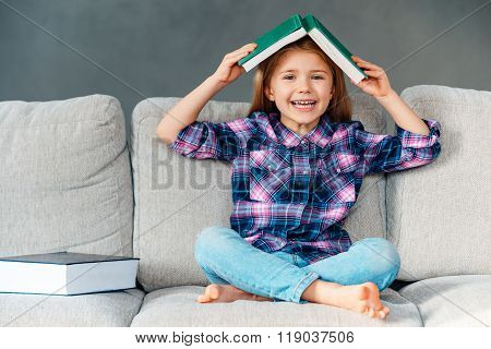 Knowledge assimilate better this way! Cheerful little girl holding book over her head and looking at camera with smile while sitting on the couch in lotus position at home