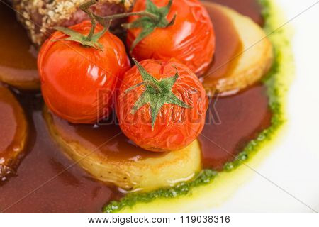 Tomatoes confit and baked potatoes close up.