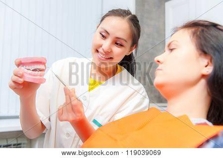 Dentist show dentures to a patient